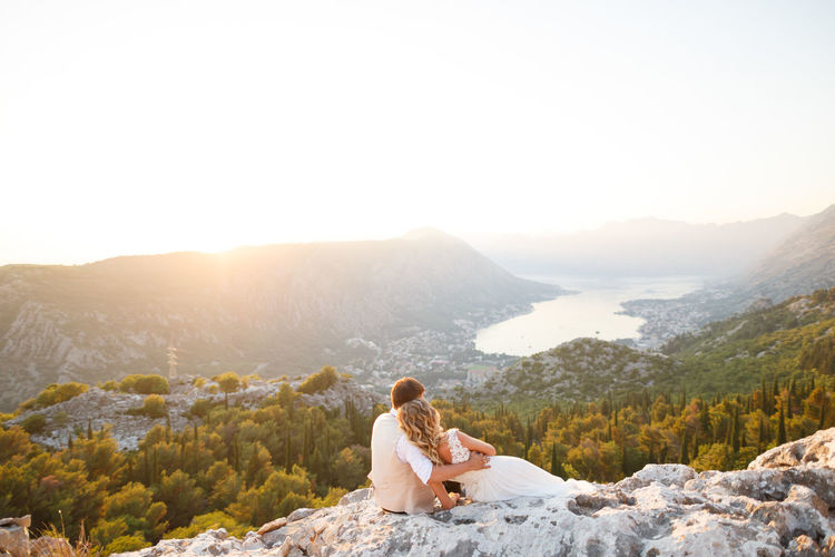 Woman sitting on mountain against clear sky