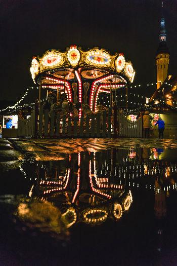 Illuminated carousel in amusement park against sky at night