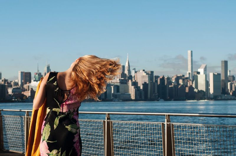 Rear view of woman standing by railing against clear sky