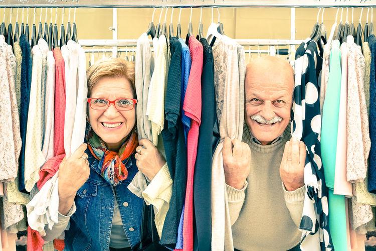 Portrait of smiling senior couple amidst clothes