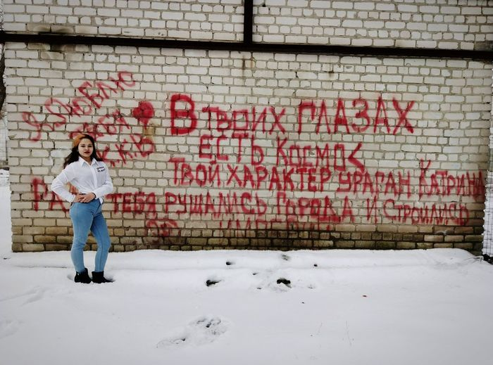 Full length of woman standing on snow against graffiti wall