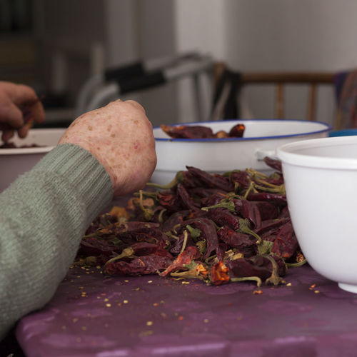 Cropped hands with red chili peppers on table