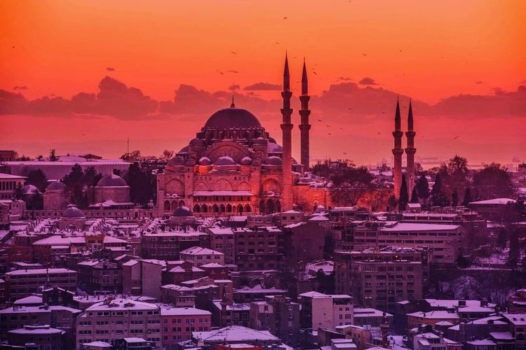 Suleymaniye mosque amidst buildings against sky during sunset