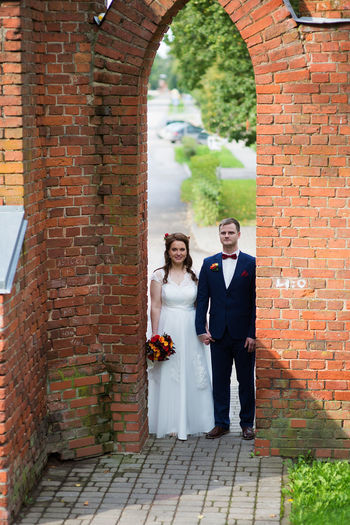 Bride and groom standing at archway