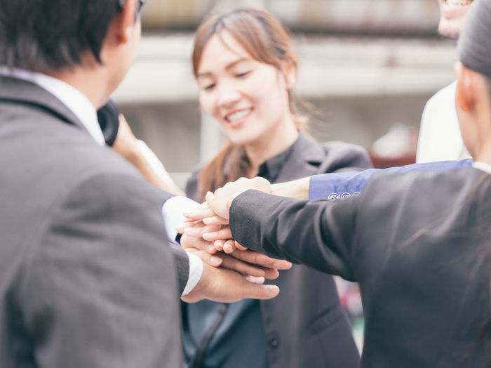 Midsection of business people giving fist-bump while standing outdoors