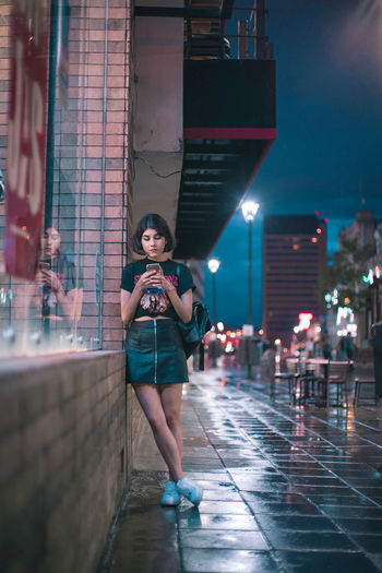 waiting Architecture Beautiful Woman Casual Clothing City Front View Full Length Holding Illuminated Leisure Activity Lifestyles Mobile Phone Night One Person Outdoors Real People Standing Street Technology Telephone Wireless Technology Young Adult Young Women