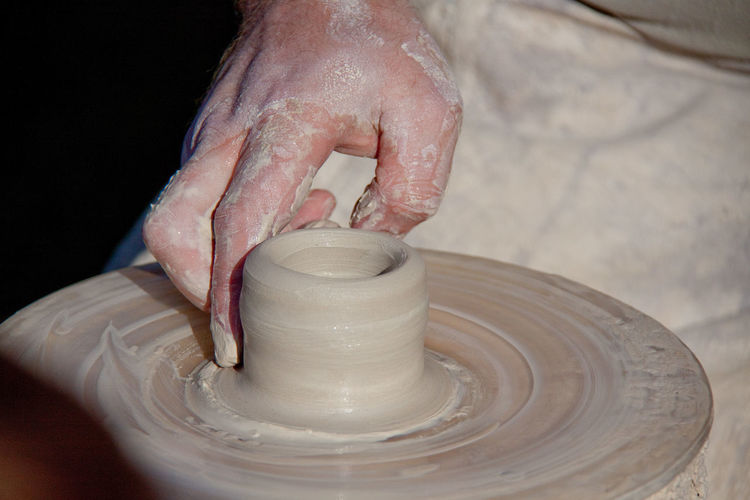 Cropped Image Of Craftsperson Shaping Clay On Pottery Wheel