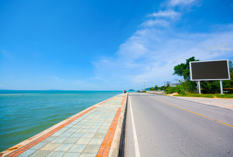 BLACK LED ELECTRONICS BOARD BESIDE SEASIDE ROAD IN BLUE SKY SUNNY DAY LED Beauty In Nature Billboard Blue Cloud - Sky Day Monitor Nature No People Outdoors Road Scenics Sea Sky The Way Forward Tree Water