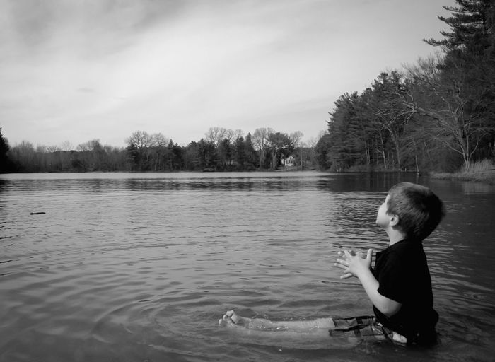 Side view of boy sitting by lake against sky