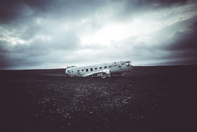 Abandoned Airplane At Beach Against Cloudy Sky