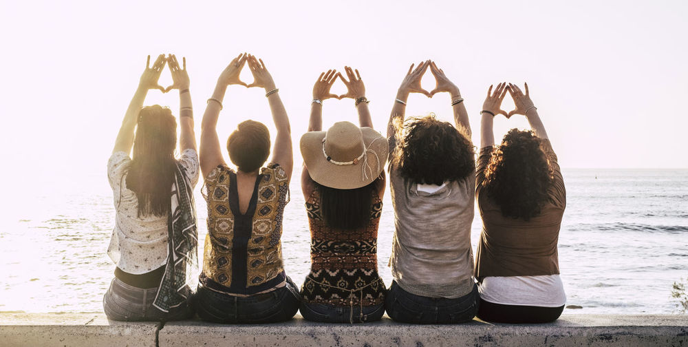 Group of young activist women viewed from rear doing feminism symbol and female power and respect with hands - sun and outdoor nature and sunset in background for group people Group Of People Water Women Rear View Leisure Activity Sky Real People Friendship Adult Lifestyles Sea Togetherness Nature Bonding Beach Side By Side Child Men Land Arms Raised Positive Emotion Human Arm Outdoors Five People Heart Shape Enjoying Life Emotion Positive Vibes Horizon Over Water Seascape Sitting Caucasian Casual Clothing Demonstration Activity