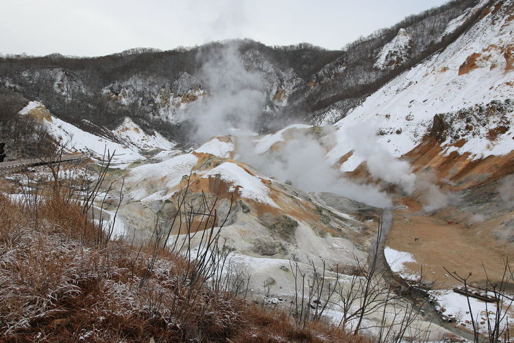 Smoke emitting from volcanic geyser against sky