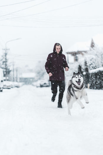 Husky Winter Cold Temperature Snow Dog Canine One Animal Mammal Domestic Animal Themes Pets Domestic Animals Animal Real People Young Adult Vertebrate Warm Clothing Full Length One Person Clothing Snowing Extreme Weather