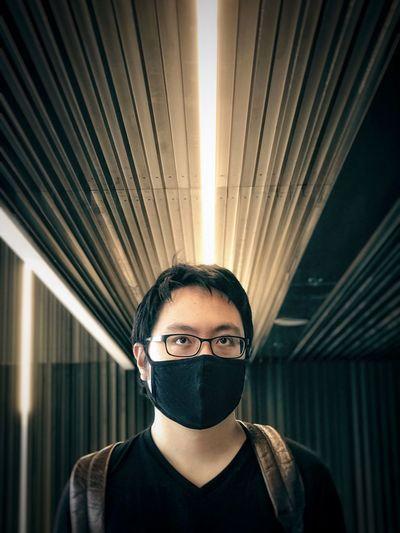 Portrait of young man standing in corridor
