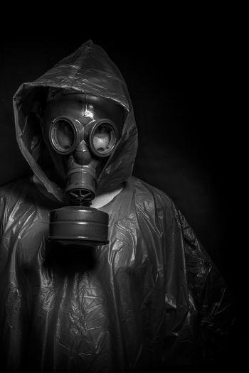 Man wearing gas mask against black background