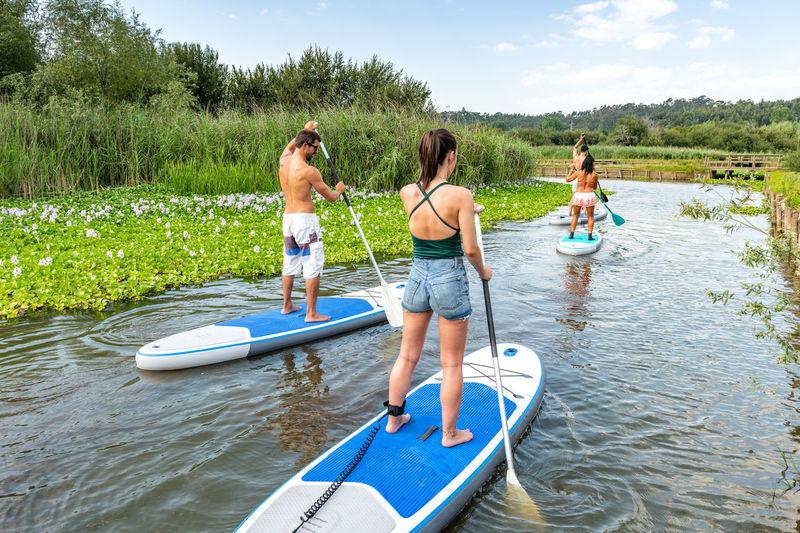 Full length of friends paddleboarding on lake