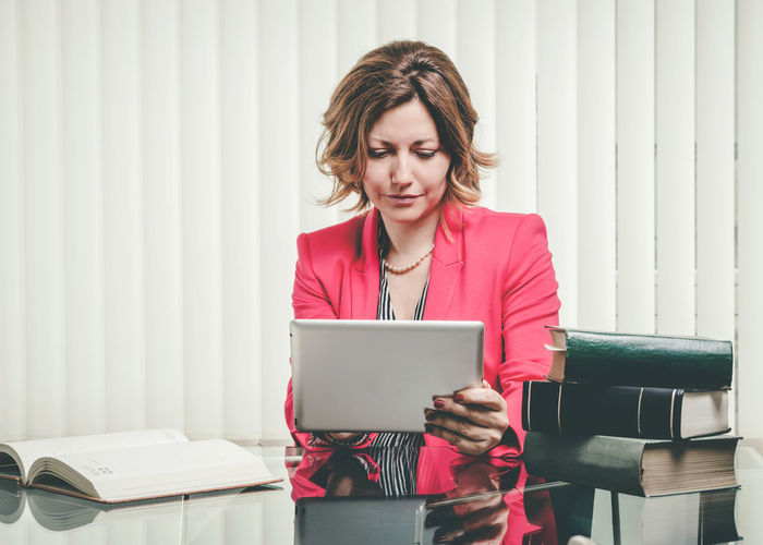 Businesswoman using digital tablet while sitting in office