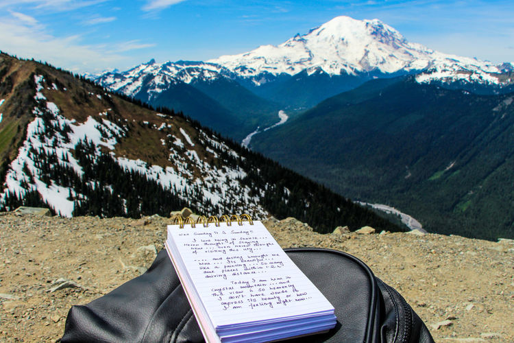 Scenic view of snowcapped mountains with someone writing blog
