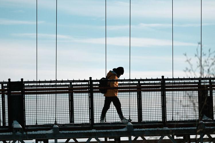 Side view of man walking on bridge against sky