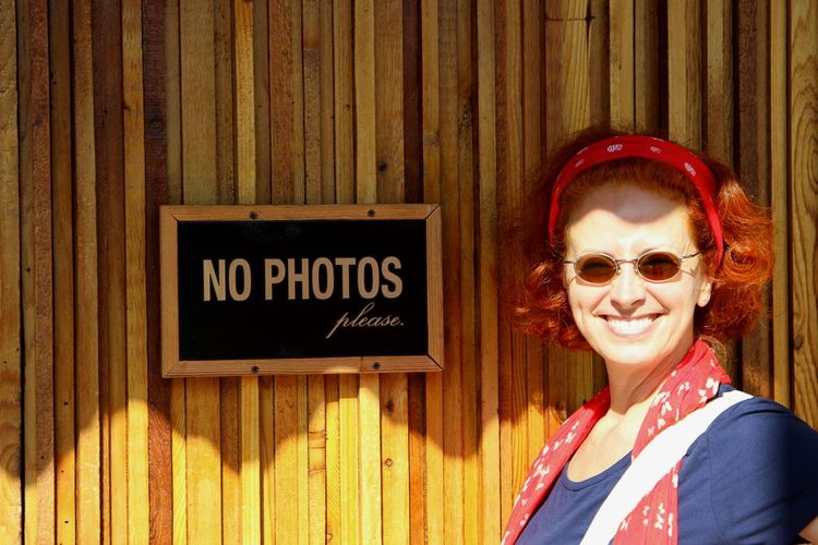 Portrait of smiling woman standing by text on wooden wall