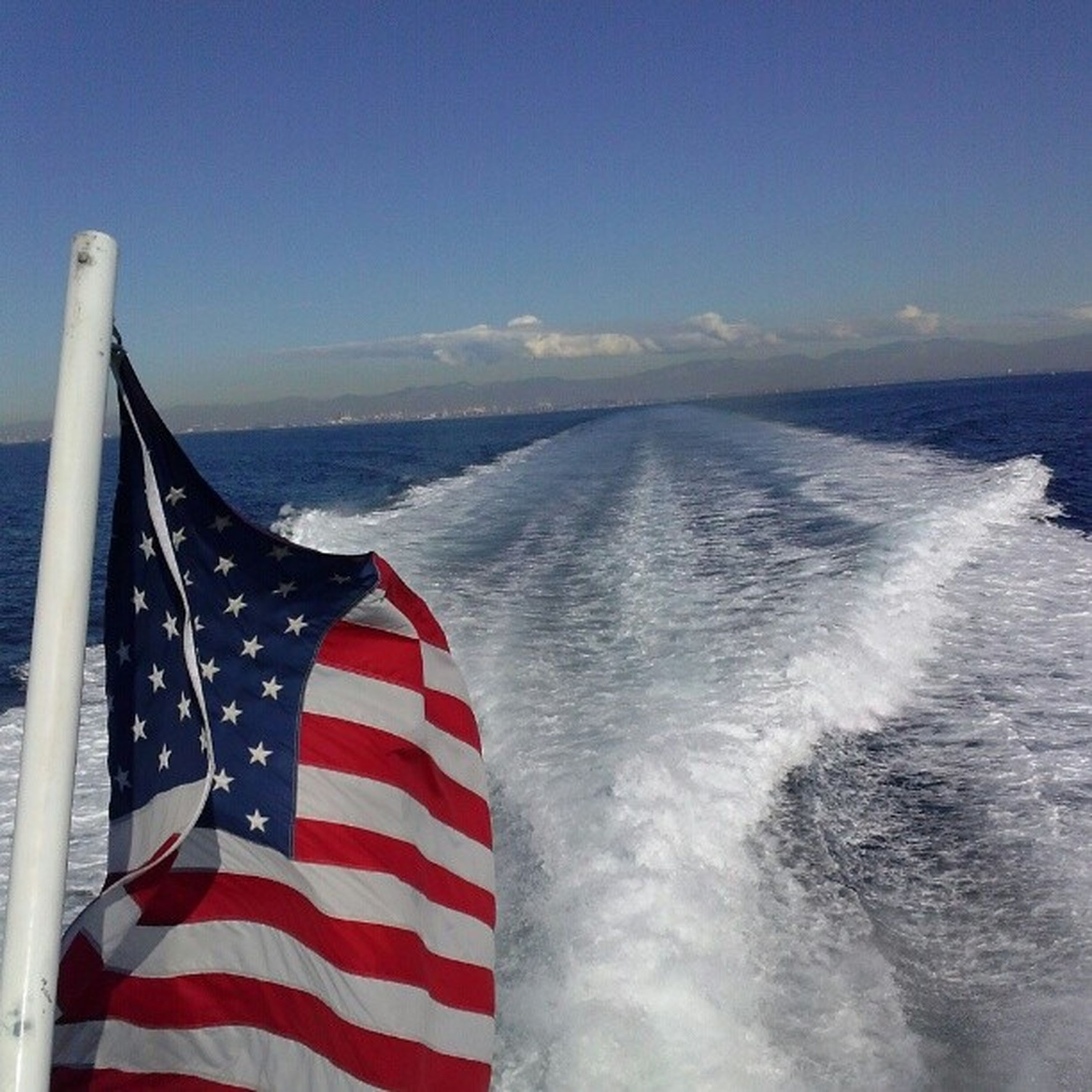 sea, flag, patriotism, identity, national flag, red, sky, american flag, wind, white color, striped, horizon over water, blue, water, scenics, day, nature, outdoors, beauty in nature, culture