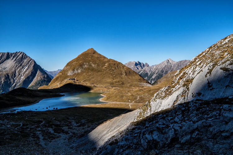 Idylic mountain lake in autumn Mountain Scenics - Nature Sky Beauty In Nature Mountain Range Clear Sky Environment Landscape Nature Tranquil Scene Non-urban Scene Blue Water No People Tranquility Lake Day Remote Copy Space Outdoors Mountain Peak Formation Mountain Lake Light And Shadow Autumn Tyrol Alps Austria The Great Outdoors - 2019 EyeEm Awards