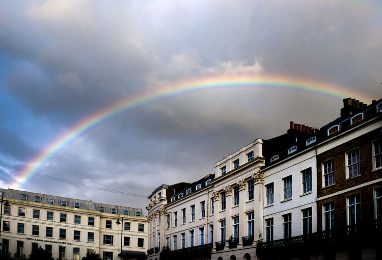 A long curved rainbow in a grey stormy sky above historic regency city houses in Brighton City Centre British House Buildings City Life Colours Of Life Colours Of Nature Historical Sights Historicbuildings Rainy Day Rainy Days Regency Architecture Stormy Skies Tourist Destination Tourist Resort Urban Landscape Urban Lifestyle Weather Weather Photography