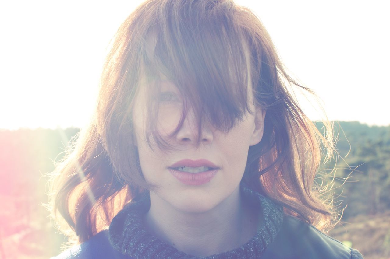 Portrait Of Woman With Tousled Hair Against Sky