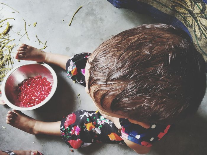 High angle view of baby girl having pomegranate seeds in bowl on floor