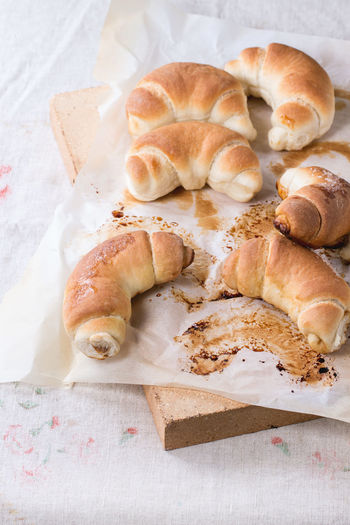Fresh homemade baked crescent rolls on baking paper and oven stone over Baked Bakery Baking Paper Bread Bread Rolls Crescent Food Fresh Baked Bread Homemade Bread Homemade Food Rolls Stone Sugar Sweet Bun Table Tablecloth White