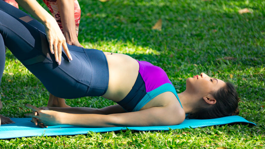 beautiful women yoga in the Park Adult Adults Only Day Exercising Flexibility Full Length Grass Healthy Lifestyle Leisure Activity Lifestyles Lying Down Nature Outdoors People Real People Sport Sports Clothing Stretching Two People Wellbeing Women Yoga Young Adult Young Women