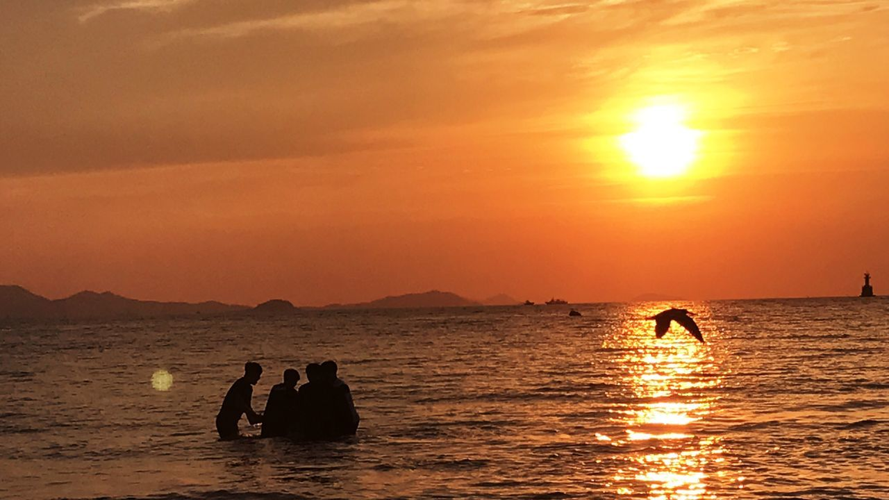sunset, silhouette, water, orange color, beauty in nature, sea, sun, nature, real people, leisure activity, scenics, sky, reflection, men, lifestyles, sunlight, outdoors, two people, adventure, horizon over water, people