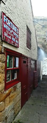 Fortunes Kippers established in 1872 sits beneath ancient cliffs in Whitby, North Yorkshire. As you walk along the cobbled Henrietta Street towards the smokehouse the beautiful oak wood aroma fills the air and your nose leads you to the tiny shop that surely must be one of the best places in Britain to buy kippers! Kipper = A freshly caught herring..split..salted..and smoked. YUMMY. Smoke Woodsmoke Architecture Business Building Old Tiny Family Run For 140 Years Shop Smokehouse Sign Text No People Window Red Painted Wood Outdoors Building Exterior Ancient Cliffs Whitby North Yorkshire