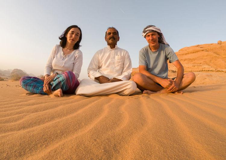 People sitting on sand at desert