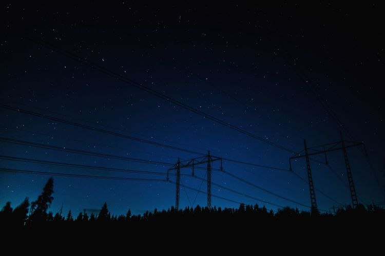 Low angle view of silhouette power line against sky at night