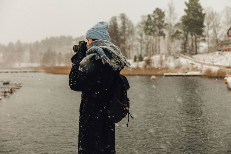 Rear view of man standing in lake during winter