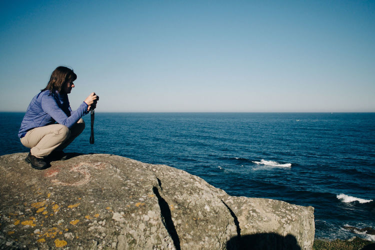 Side view of woman photographing while crouching on rocky shore