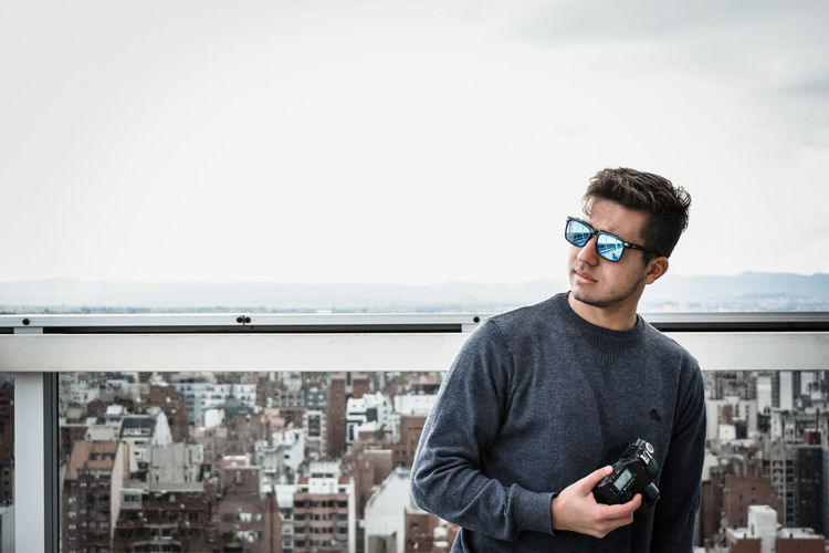 Portrait of young man photographing in city against sky