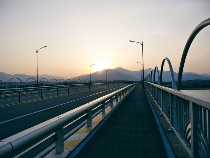 Bridge over road against sky during sunset
