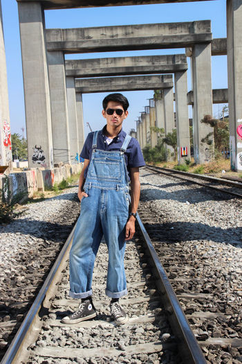 Full length of young man standing on railroad track