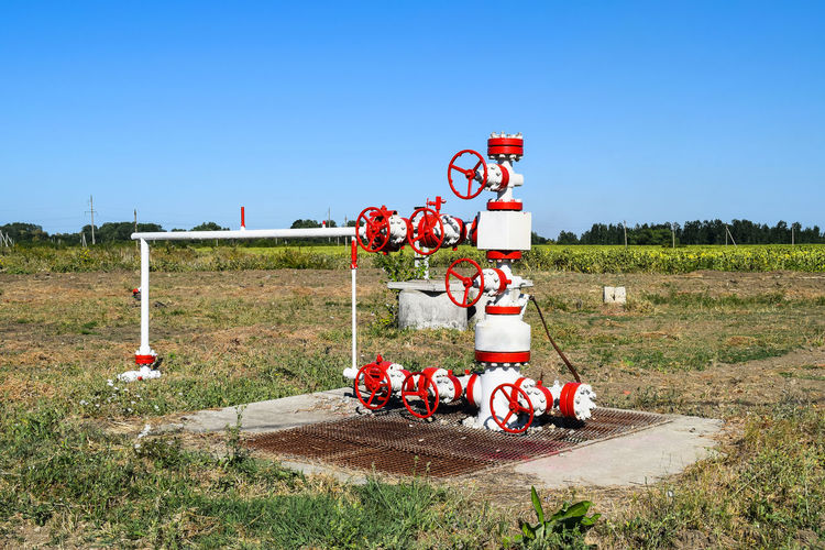 Red valves on grassy field against clear blue sky
