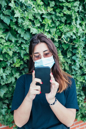 Portrait of young woman using phone while standing on plants