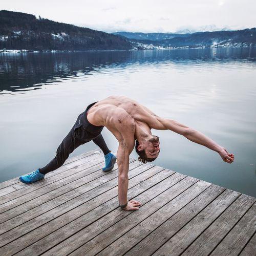 Full length of shirtless man standing on pier over lake