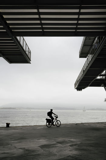 Man riding motorcycle on sea against sky
