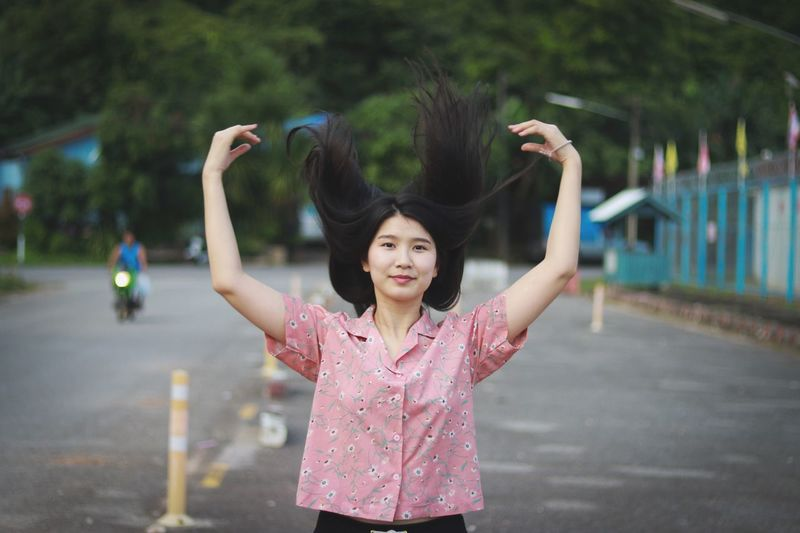 Portrait of young woman tossing hair while standing on road