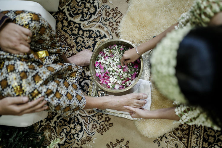 High angle view of bride washing woman legs on floor