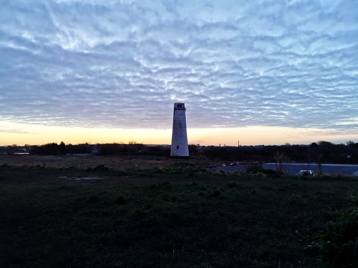 Lighthouse on field against sky during sunset