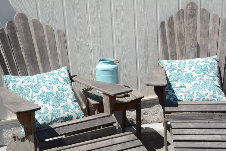 Cushions on wooden adirondack chairs against wall