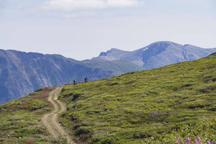 People biking on mountain against sky