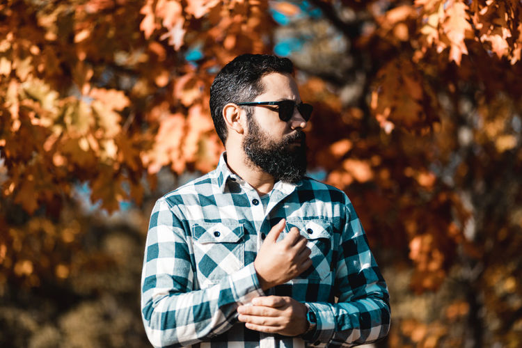 Man wearing sunglasses looking away while standing against trees